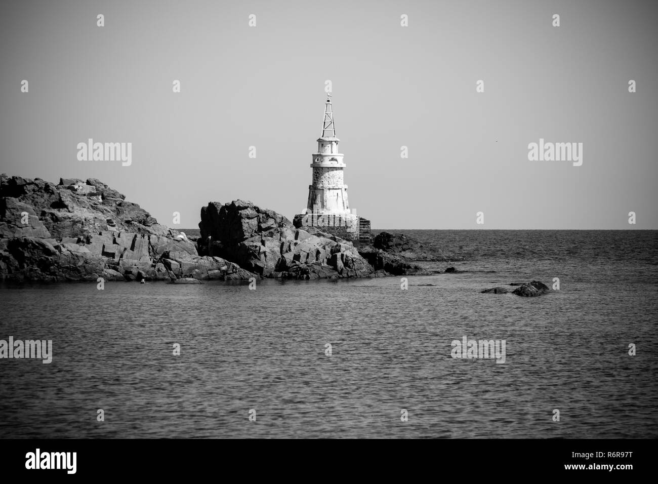 A lighthouse on the rocks. Black Sea. Ahtopol. Bulgaria. Black and white. - Stock Image
