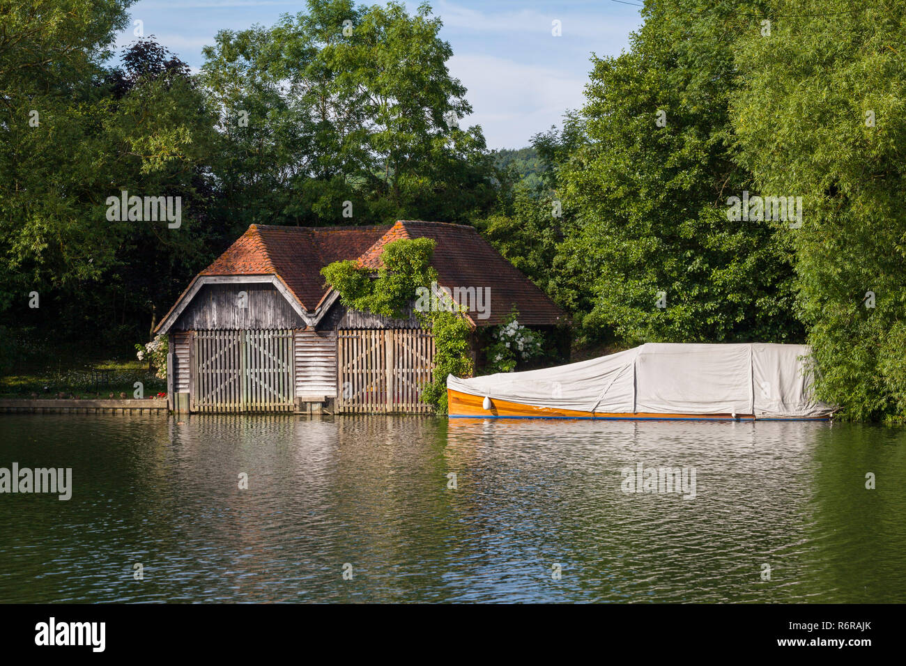 An old boathouse and classic mahogany launch under a canvas cover on the Thames at Mill End, Buckinghamshire - Stock Image