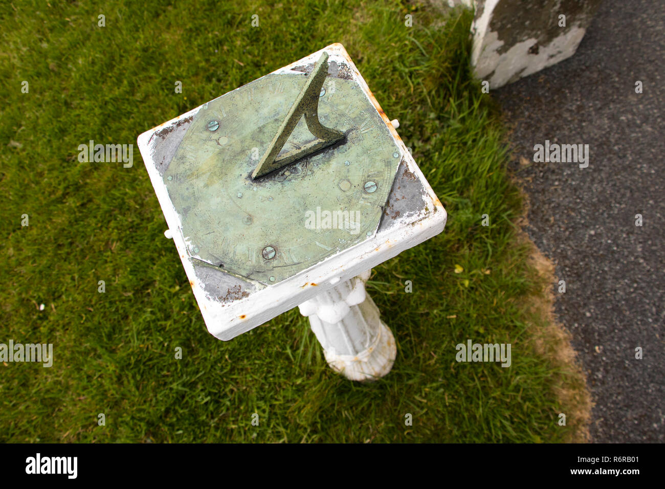 Copper horizontal Sun dial with inclined edge on pedestal in garden - Stock Image
