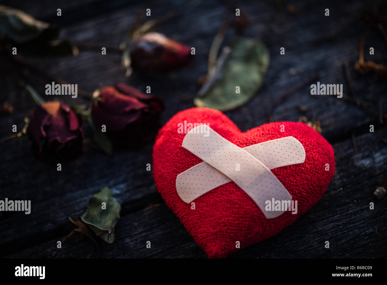 First Aid Band Cushioned Plaster Strip Medical Patch glued on red heart with dried red rose on wooden background. Heart broken, Love and Valentines day concept. - Stock Image