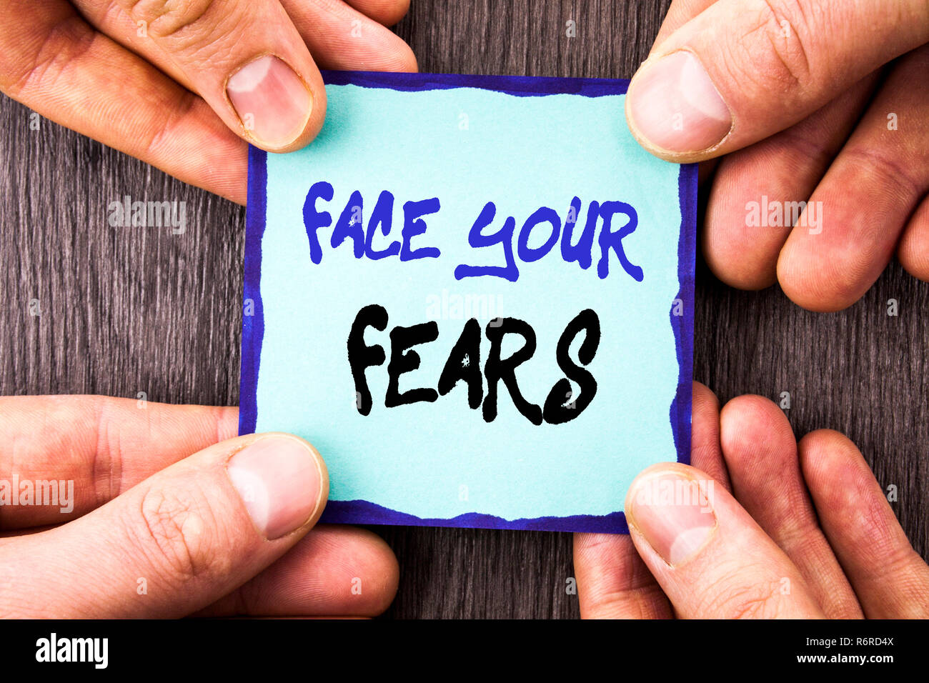 Handwriting Announcement text showing Face Your Fears. Conceptual photo Challenge Fear Fourage Confidence Brave Bravery written on Sticky Note Paper Holding Hand with Finger. Stock Photo