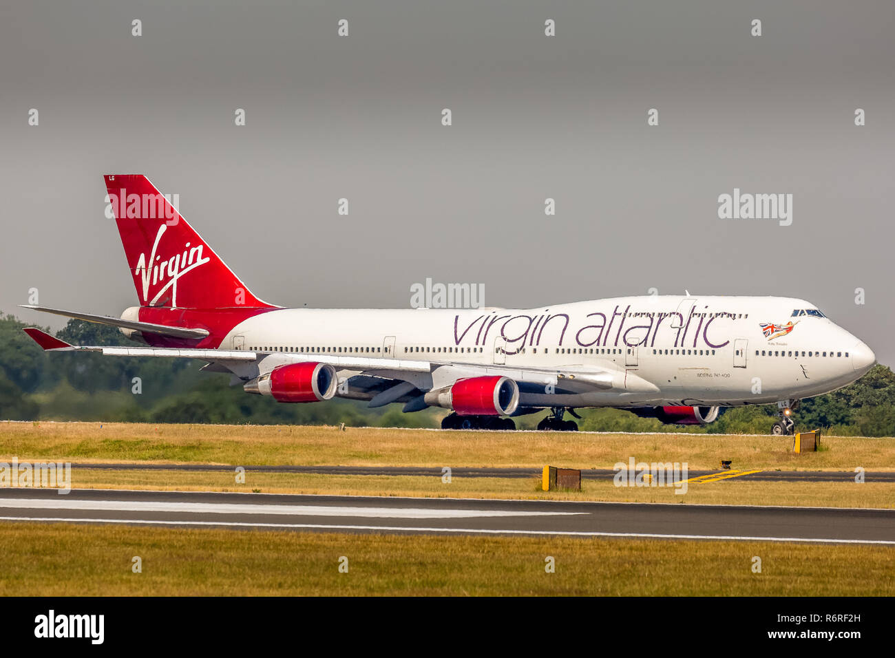 A Virgin Atlantic Airways Boeing 747-400, registration G-VXLG, taxying back to then terminal at Manchester Airport in England after landing. - Stock Image