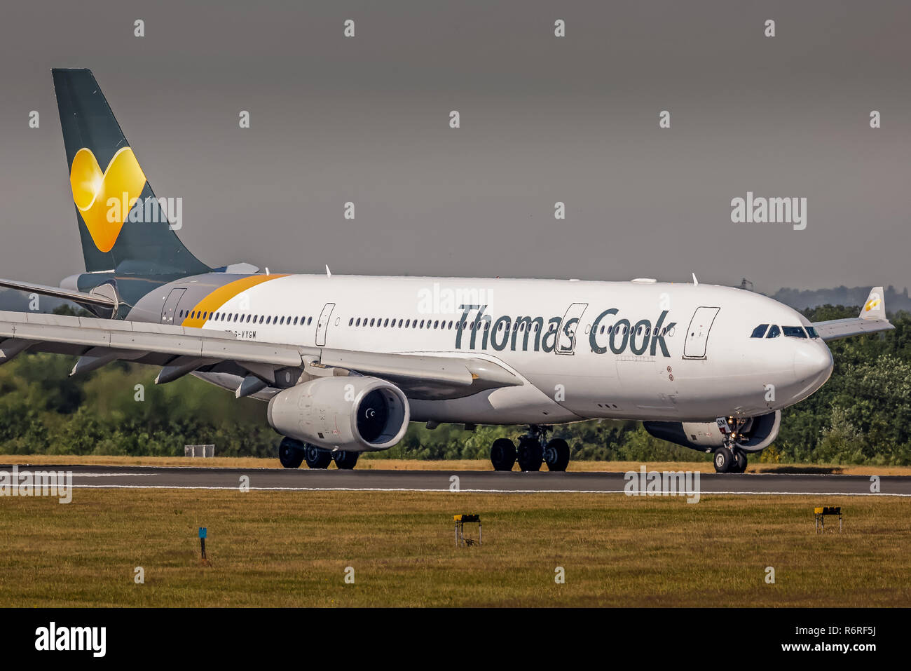 A Thomas Cook airlines Airbus A330, registration G-VYGM, taking back to the terminal at Manchester Airport in England after landing. - Stock Image