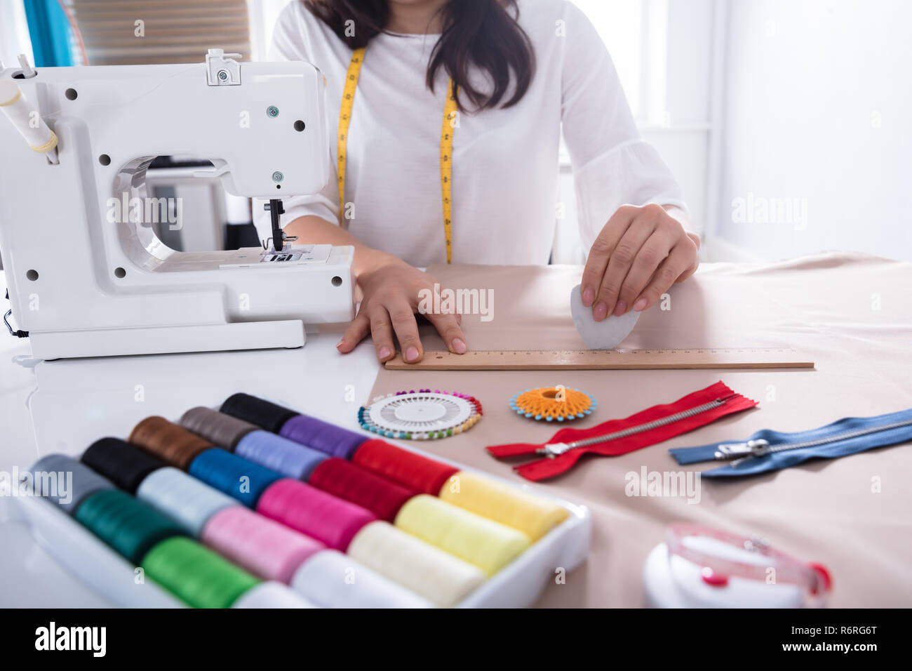Fashion Designer Measuring Fabric With Ruler - Stock Image