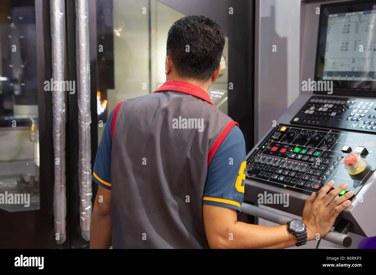 Industrial worker input data programing for CNC milling machine - Stock Image