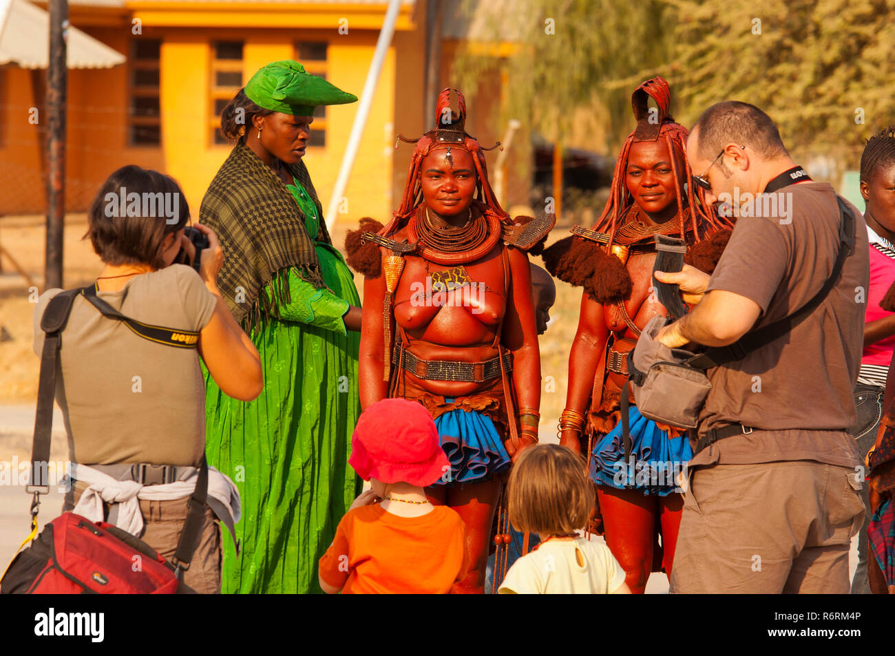 Tourists taking pictures of  two Himba womans on the streets of Opuwo town, northern Namibia - Stock Image