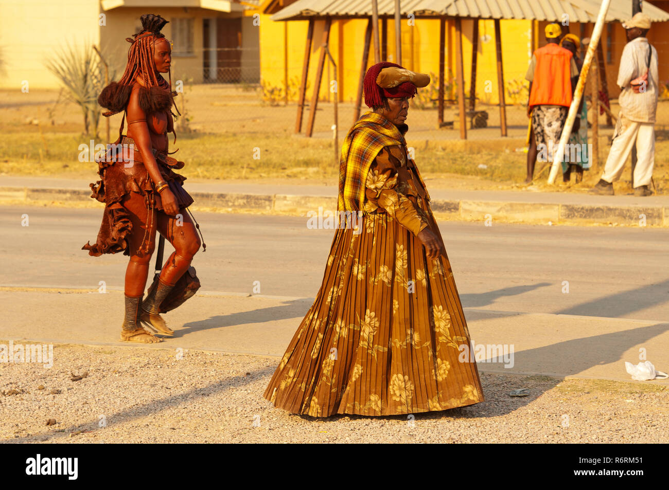 A Himba and Herero womans in full regalia walking at the streets of Opuwo, Namibia - Stock Image