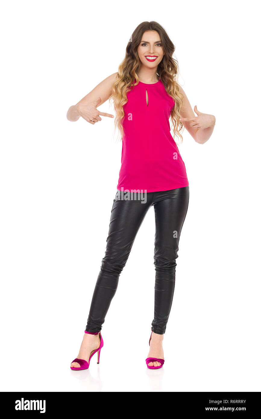 5daf561b573 Smiling beautiful young woman in pink top, black leather pants and ...