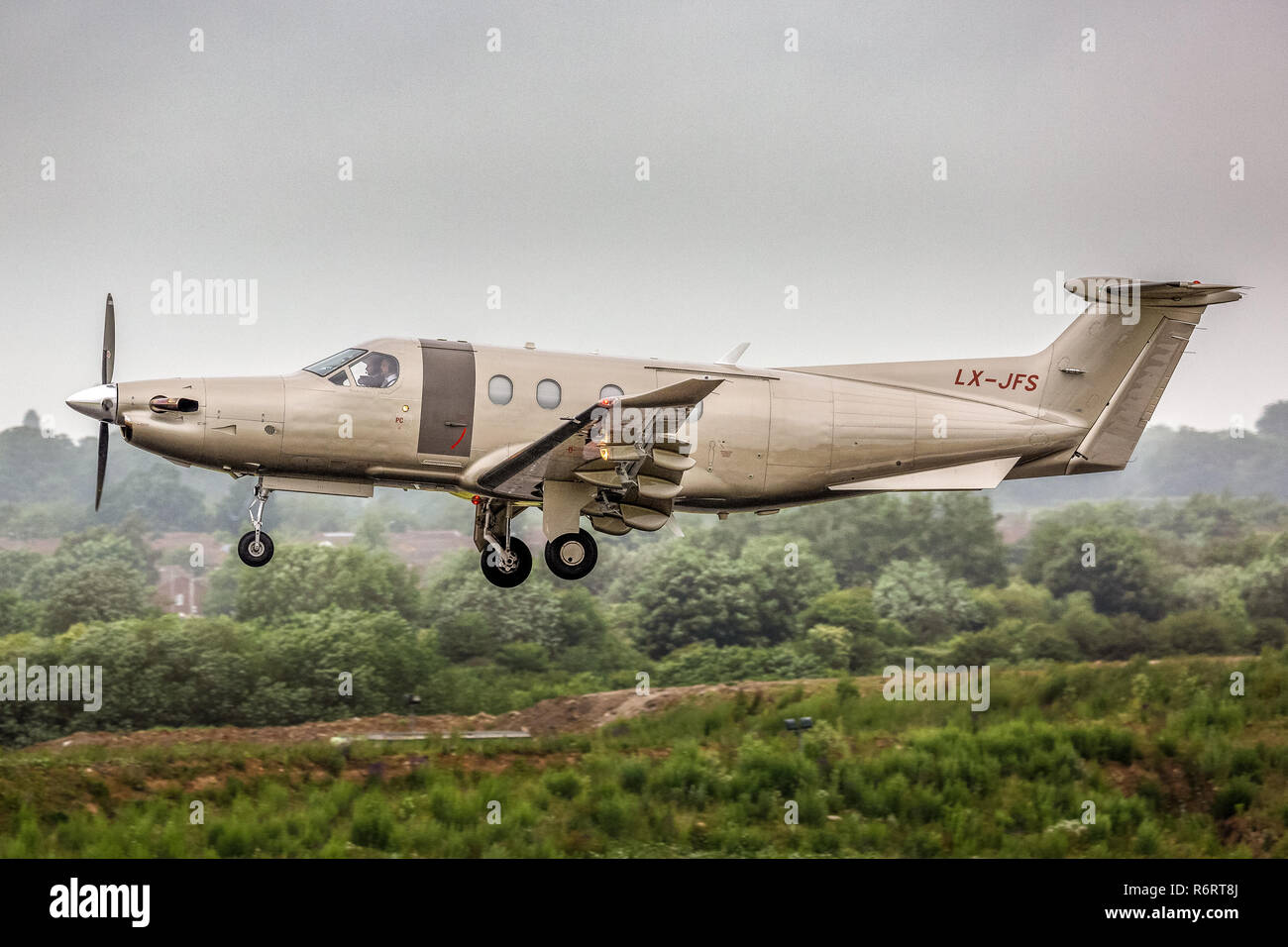 A Pilatus PC-12 turboprop executive aircraft, registered in Luxembourg as LX-JFS, taking off from London Luton Airport in England - Stock Image