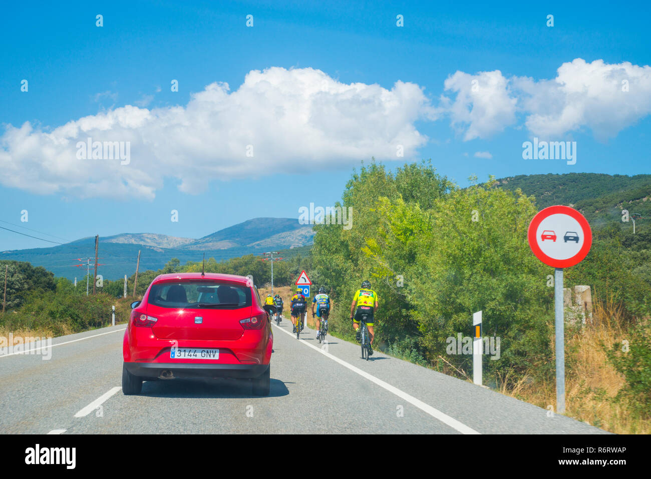 Car overtaking a group of cyclists with prohibition traffic sign. - Stock Image