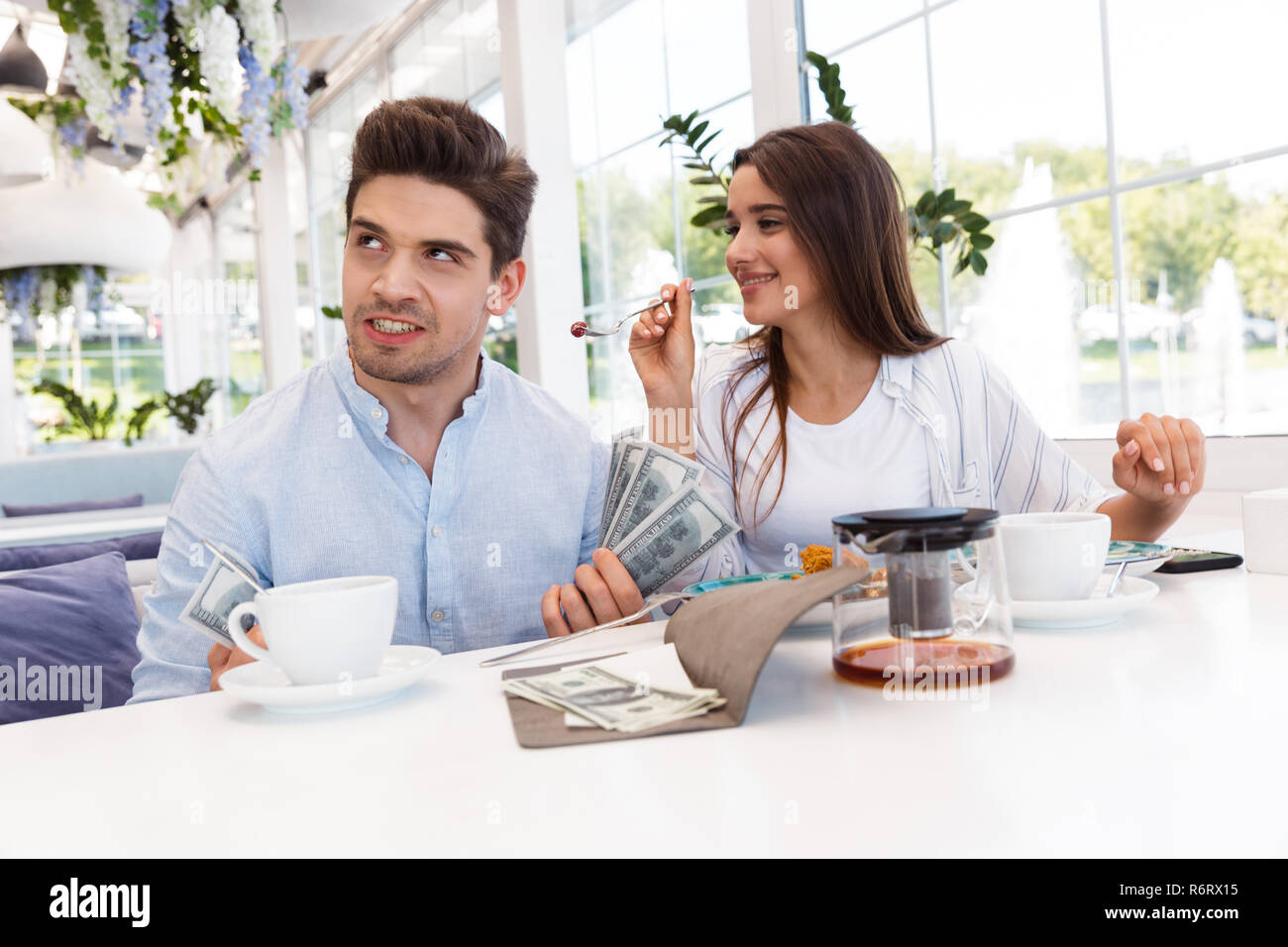 Image of a young displeased confused loving couple sitting in cafe holding check and money. - Stock Image