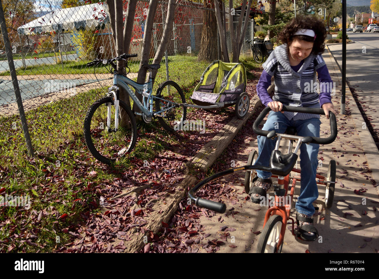 An example of community inclusion, a young woman with special needs rides an adaptive bike in her bike-friendly Colorado community. - Stock Image