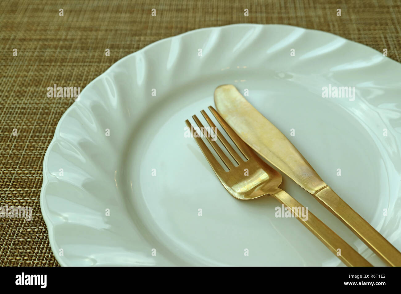 Closed Up White Ceramic Plate and Brass Cutlery on Beige Luncheon Mat - Stock Image