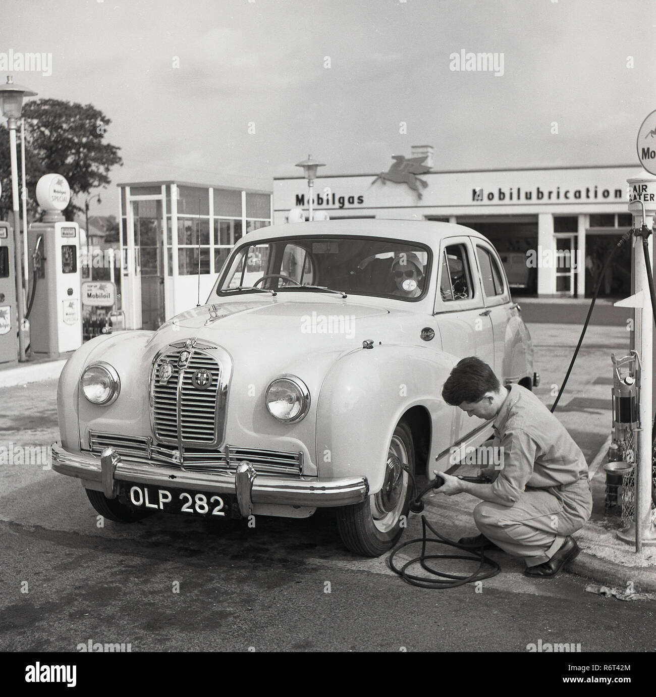 1950s, historical, the golden days of motoring, a young male service station sttendant checks the tyre pressure on an Austin car parked at a the fuel pumps at a Mobilgas Service Station, London, England, UK. - Stock Image