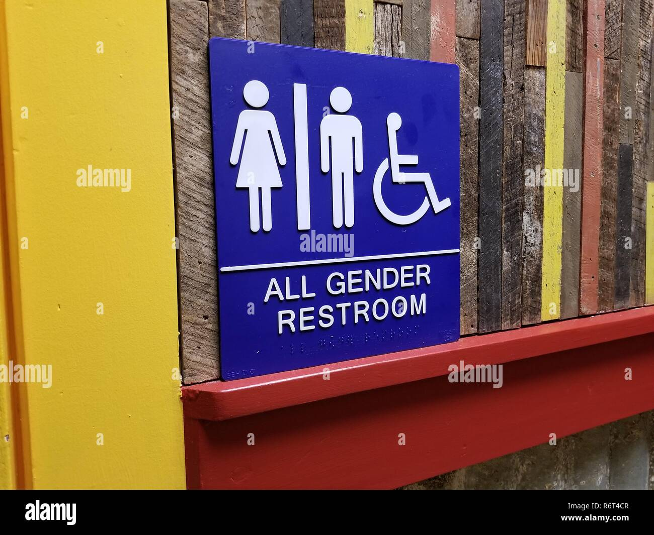 Close-up of sign for an All Gender restroom against a wooden wall with yellow doorframe visible, San Ramon, California, November 28, 2018. () - Stock Image