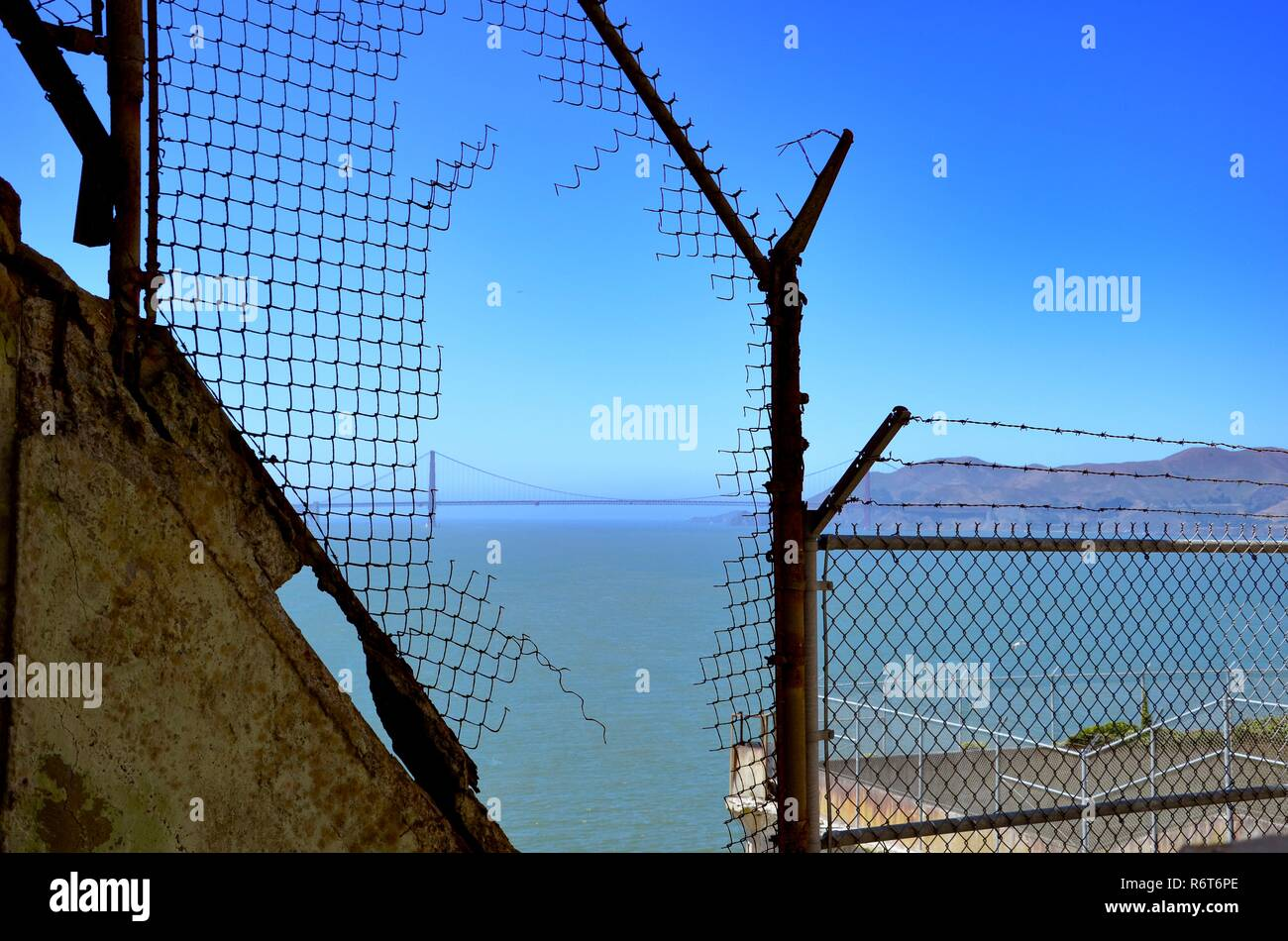 View through a torn fence on Alcatraz Island in San Francisco Bay towards Golden Gate Bridge, view outside jail - Stock Image