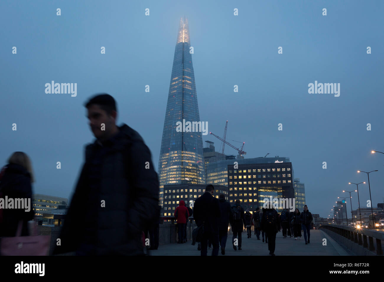 Commuters walk southwards over London Bridge towards the Shard skyscraper on a dark winter's afternoon, on 23rd November 2018, in London, England. - Stock Image