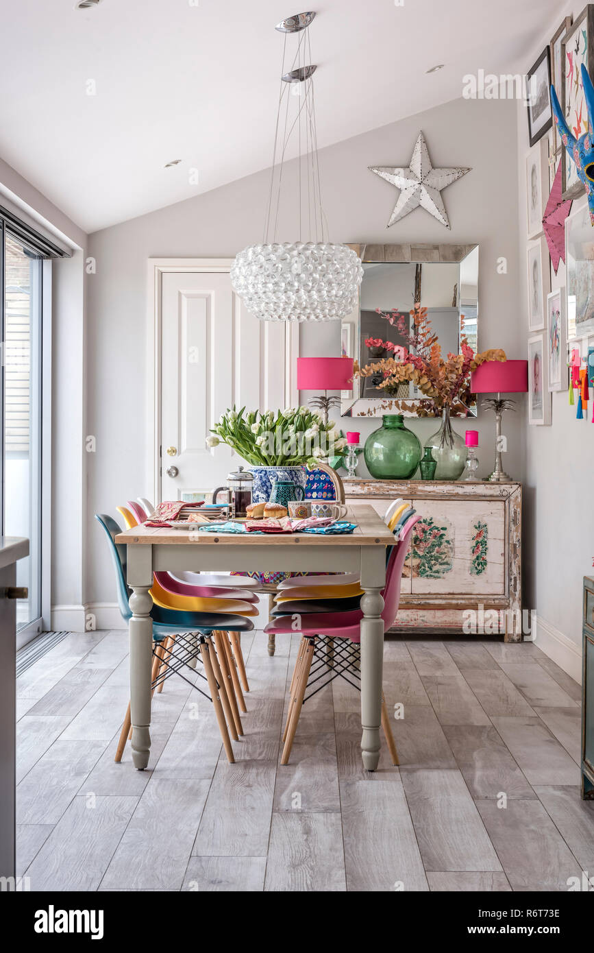 Caboche pendant above table with multicoloured Eames-style chairs - Stock Image