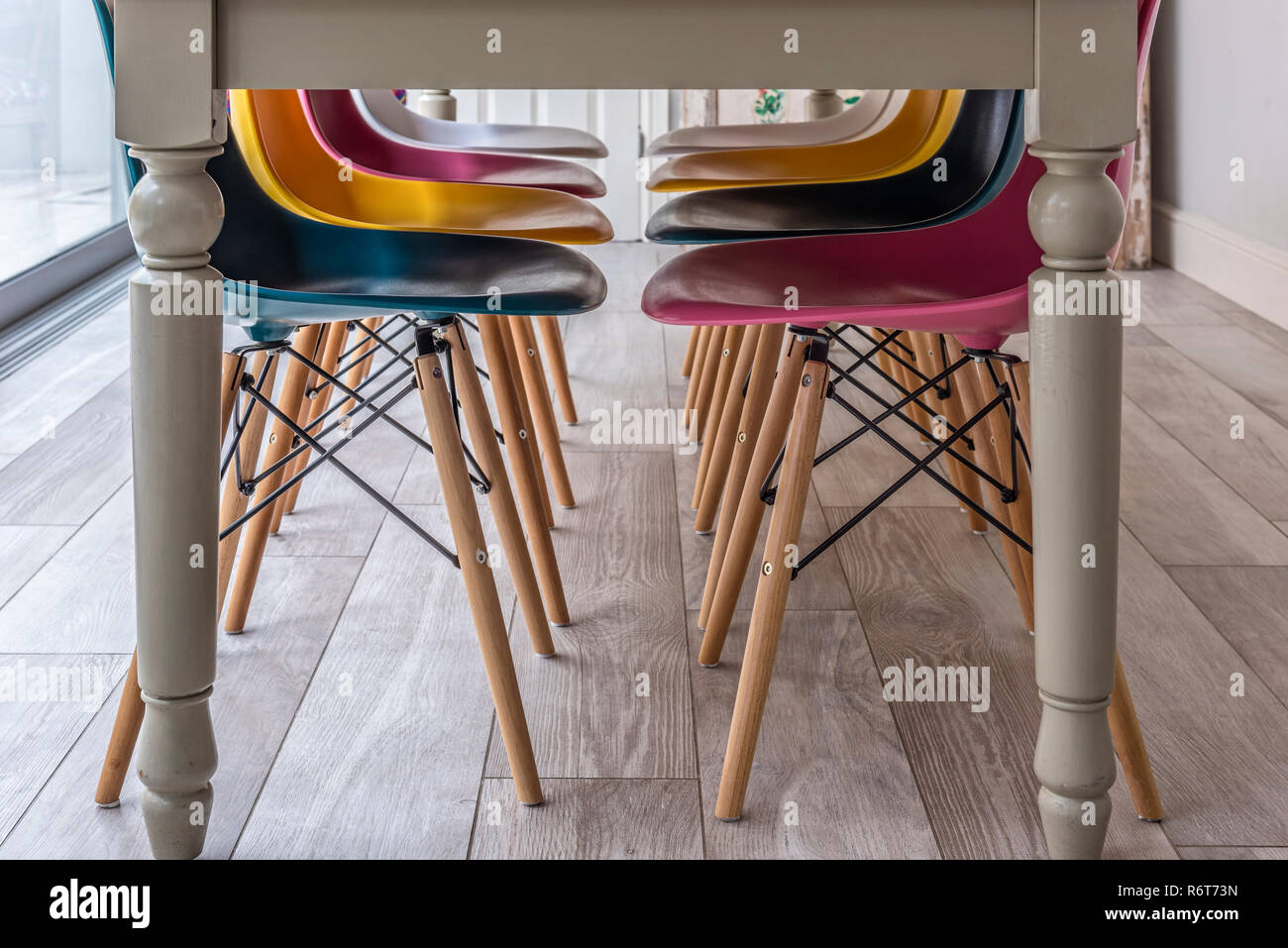 Multicoloured Eames-style chairs and table legs - Stock Image
