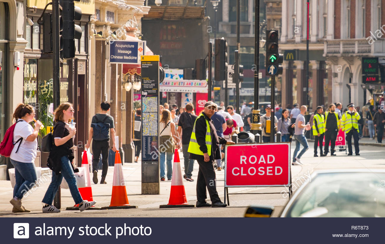 Man wearing high visibility vest standing next to Road Closed sign, Shaftesbury Avenue, City of Westminster, London, England, United Kingdom - Stock Image