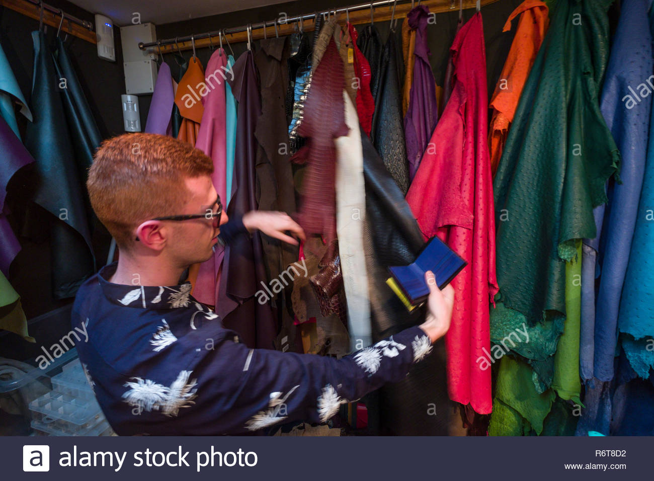 Salesman showing various colors and types of leather and lizard skins inside Pickett London, provider of handmade luxury leather goods, Mayfair, City  - Stock Image