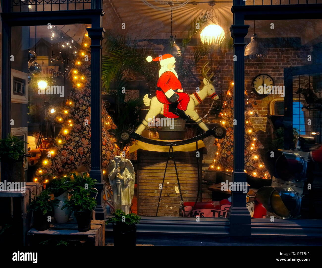 Worthing, Sussex, England. 6th December, 2018. Santa's rockin' Reindeer.Festive Christmas season antique shop window display in Rowlands Road today with vintage artifacts and Santa Claus riding an old rocking Reindeer. Photo: Jonathan Eastland/Ajax/Alamy Live News. - Stock Image