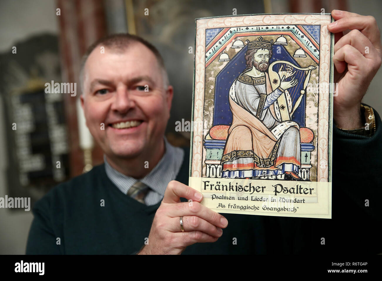"""Lichtenau, Germany. 06th Dec, 2018. Pastor Claus Ebeling holds the church dialect hymnbook """"Fränkischer Psalter - Psalmen und Lieder in Mundart - As fränggische Gsangsbuch"""" in his hands in the Trinity Church. The special hymnbook for Franconia contains not only the Franconian """"Our Father"""", but a total of 23 biblical psalms and 44 songs on 80 pages. Including dialect versions of well-known Christmas songs. (to dpa-Korr: """"Vadder unser - Franken gets church dialect songbook"""" from 07.12.2018) Credit: Daniel Karmann/dpa/Alamy Live News Stock Photo"""
