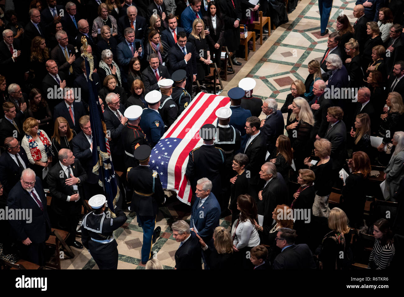 U.S. military honor guard carry the flag draped casket of former president George H.W. Bush down the aisle of the National Cathedral at the conclusion of the State Funeral December 5, 2018 in Washington, DC. Bush, the 41st President, died in his Houston home at age 94 and will be buried at his presidential library at Texas A&M University. Stock Photo