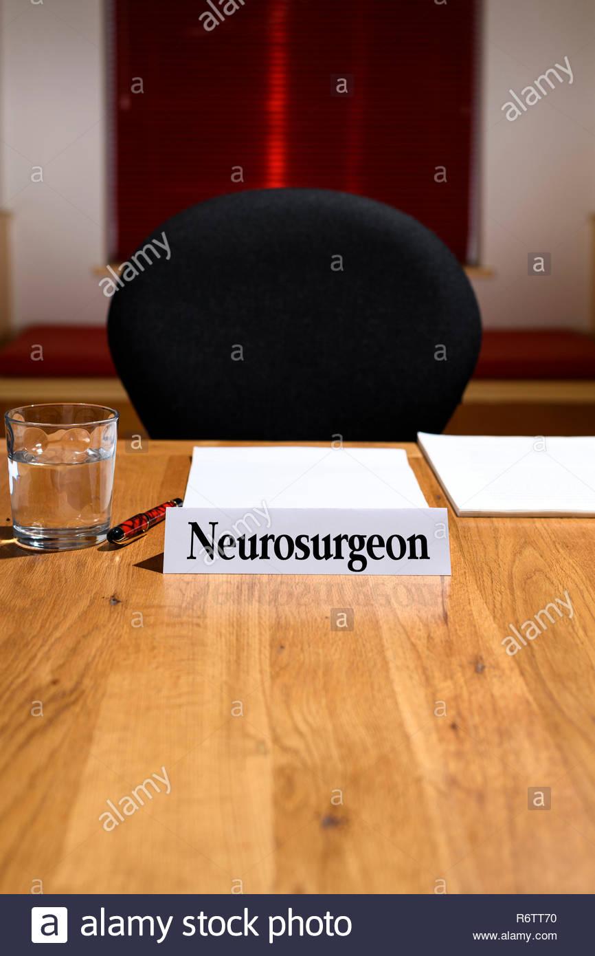 Neurosurgeon, NHS job title shown on nameplate, meeting table, England, UK Stock Photo