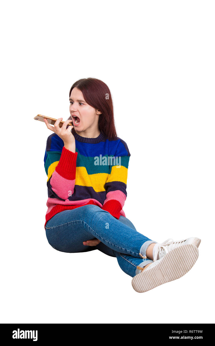 Portrait angry young woman shouting and screaming on mobile phone sitting on the floor. Negative emotions annoyed people rage grimace feelings isolate - Stock Image