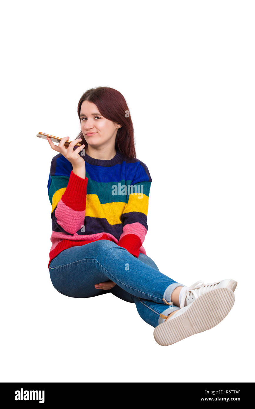 Sad and bored hipster girl holding smartphone during leisure time sitting on the floor isolated over white background. Dispirited female blogger bored - Stock Image
