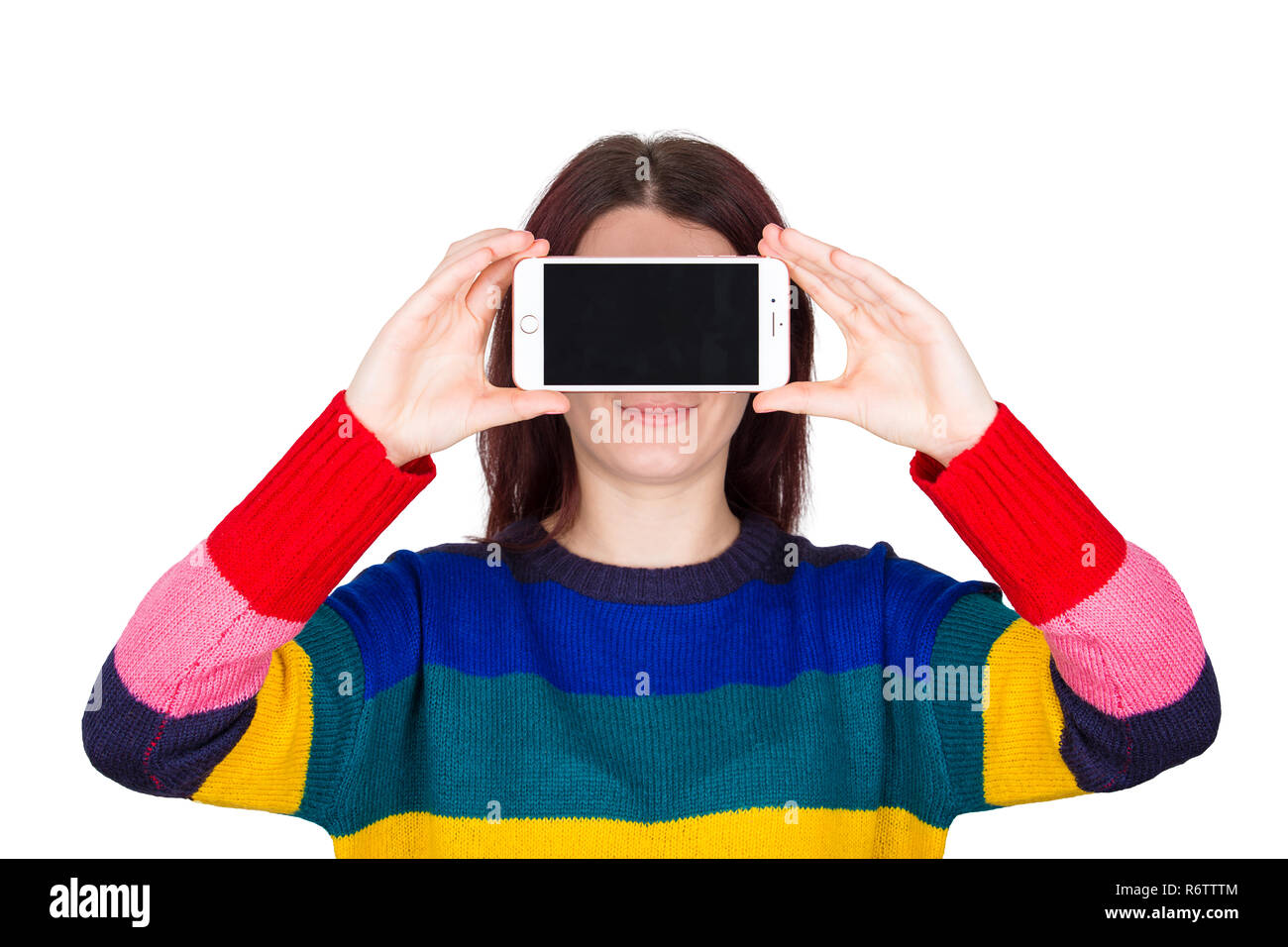 b69357306747 Happy young woman student wearing sweater holding smartphone close to eyes  like looking through virtual reality
