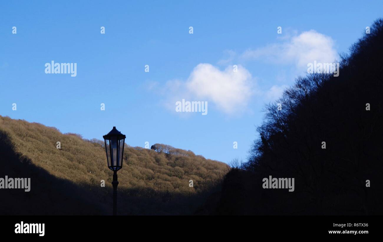 Traditional Lamppost Silhouetted against the Leafless Winter Wooded East Lyn Valley. Exmoor National Park, North Devon, UK. - Stock Image