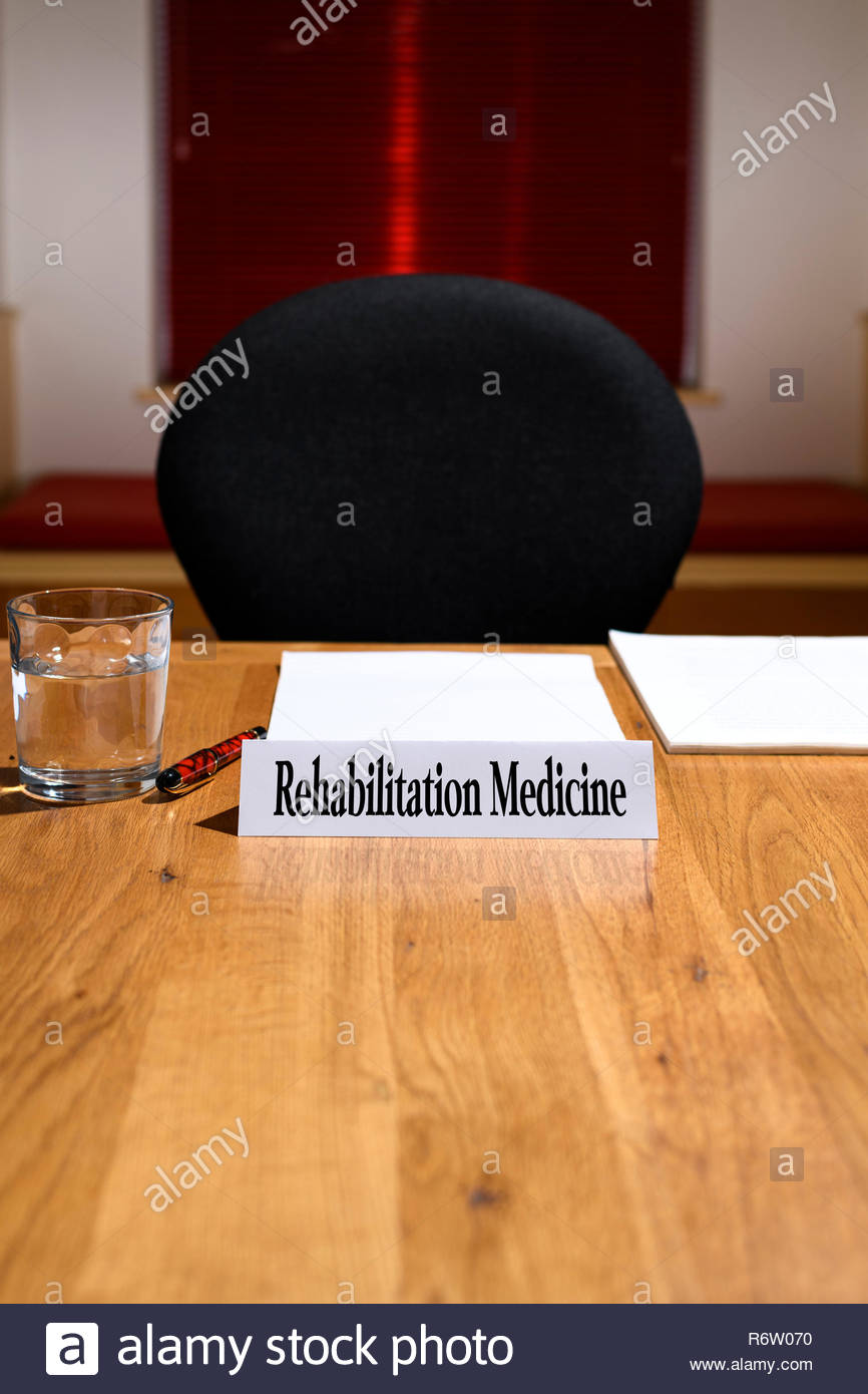 Rehabilitation Medicine, NHS job title shown on nameplate, meeting table, England, UK - Stock Image