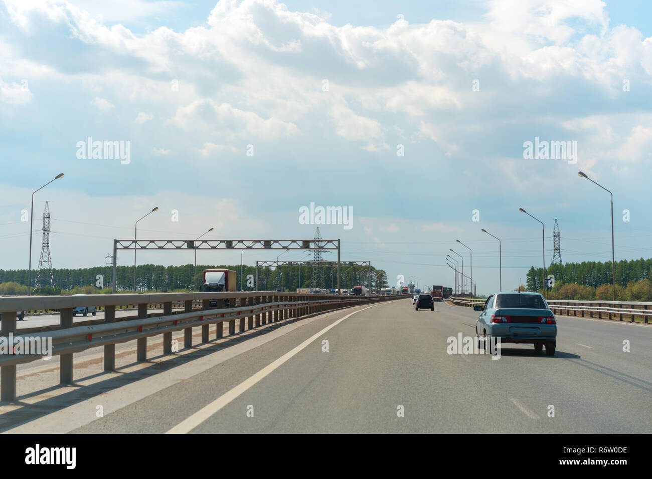 View of paved freeway with lanterns on sides and cars driving among green summer trees in cloudy day Stock Photo