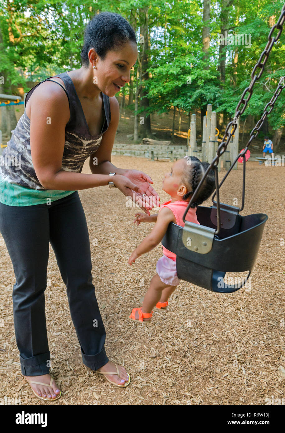 Nailah Wagner pushes her daughter, 10-month-old Emery Wagner, in a swing at Candler Park, June 4, 2014, in Atlanta, Georgia. - Stock Image
