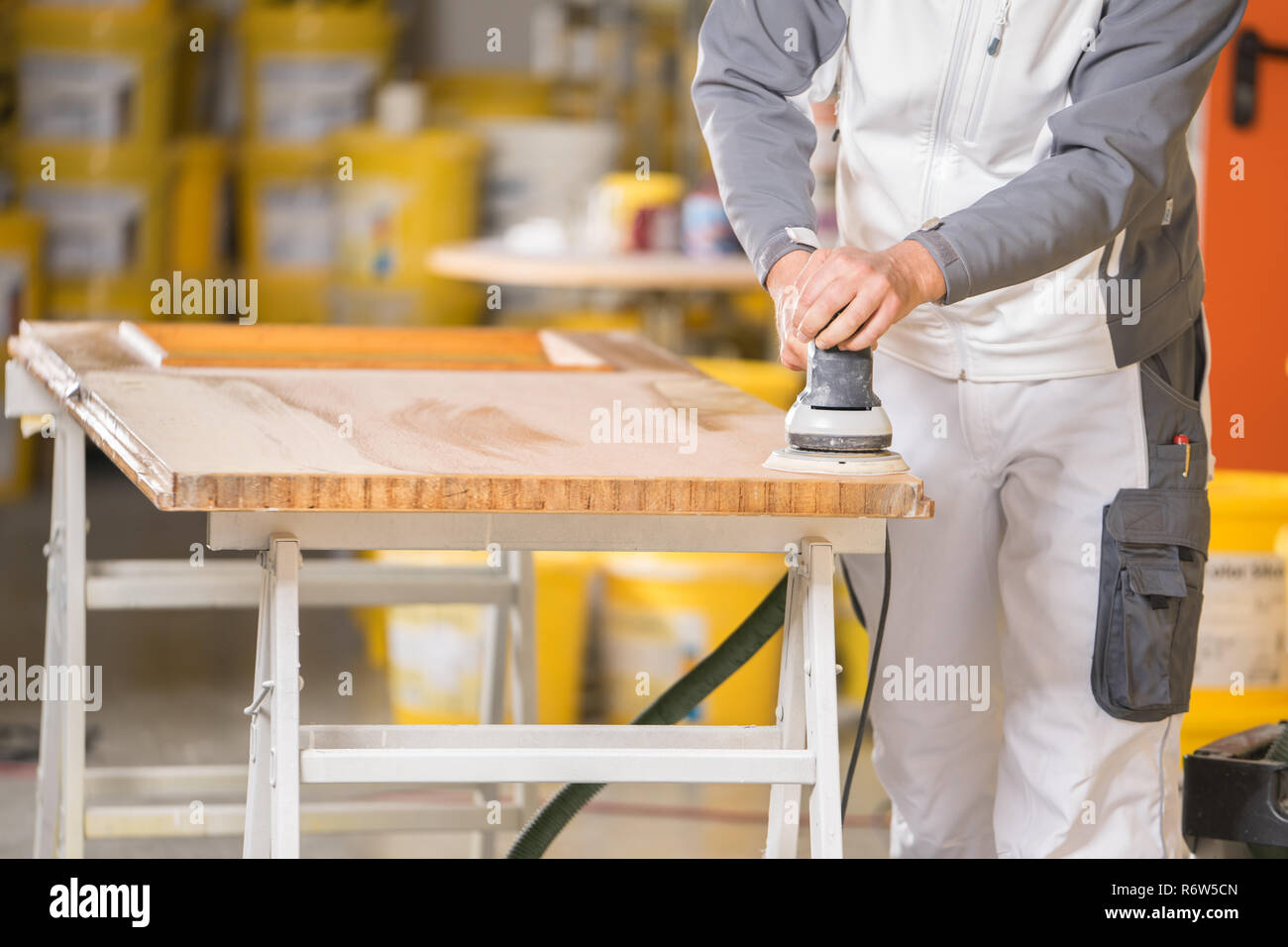 a painter at the wooden door grinding - Stock Image