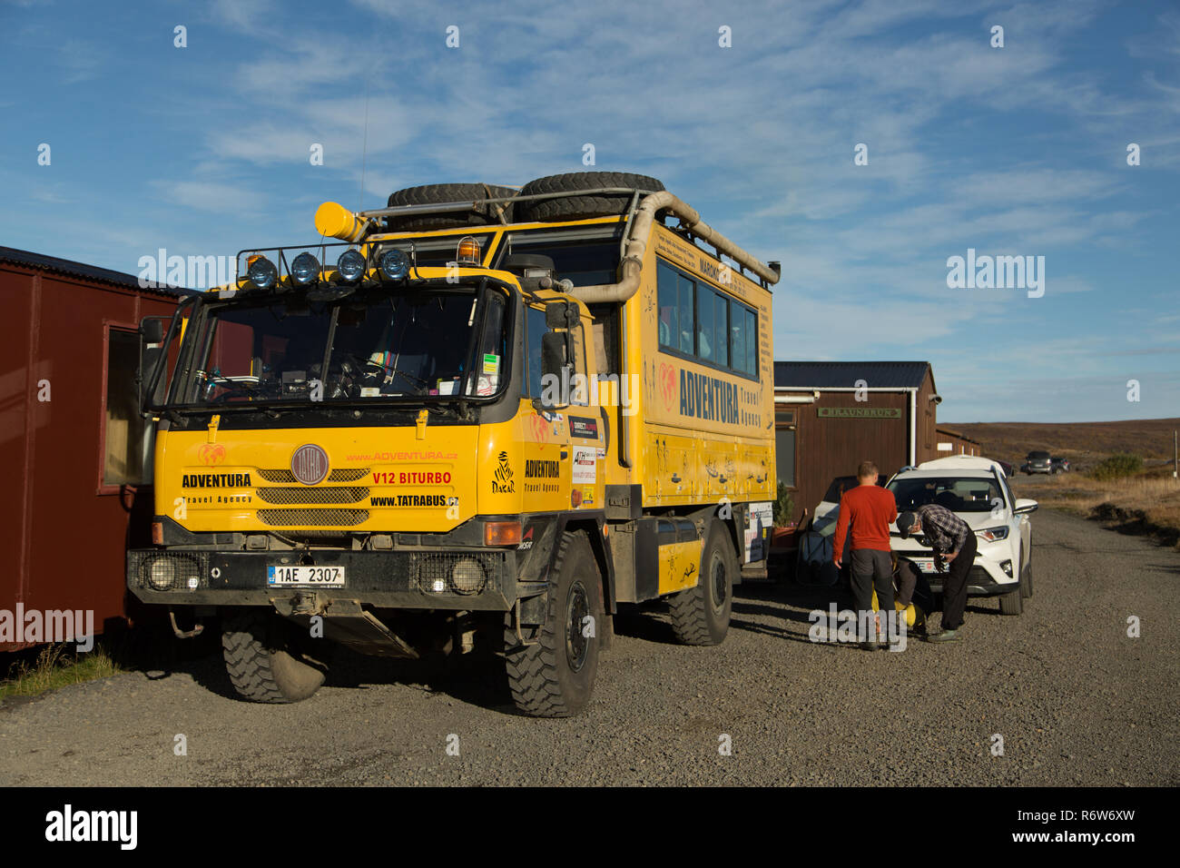 Adventura Travel Agency vehicle parked outside hostel in Lake Myvatn waiting to take tourists on sightseeing tour - Stock Image