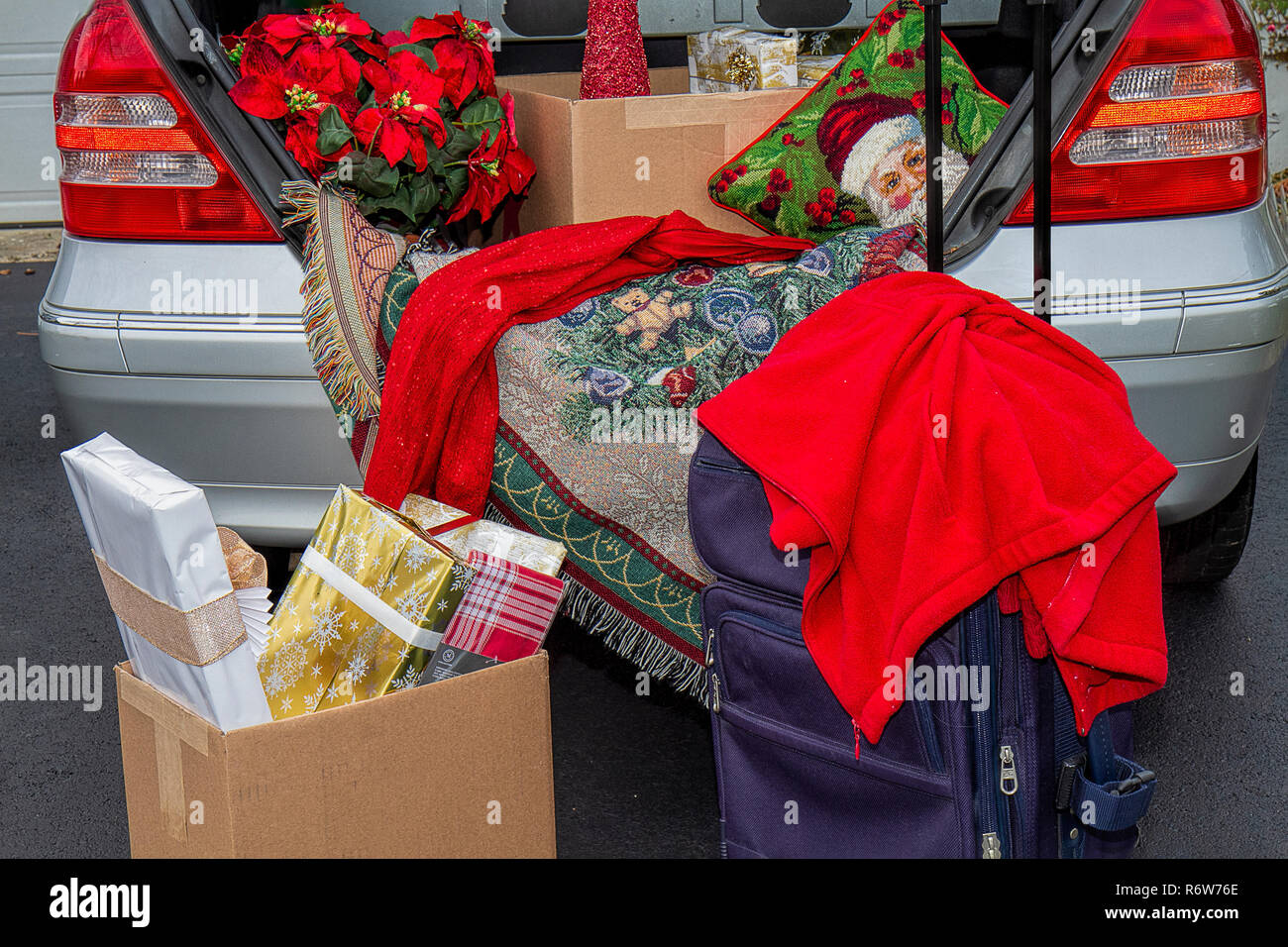 Packing trunk of car with Christmas gifts for holiday traveling - Stock Image