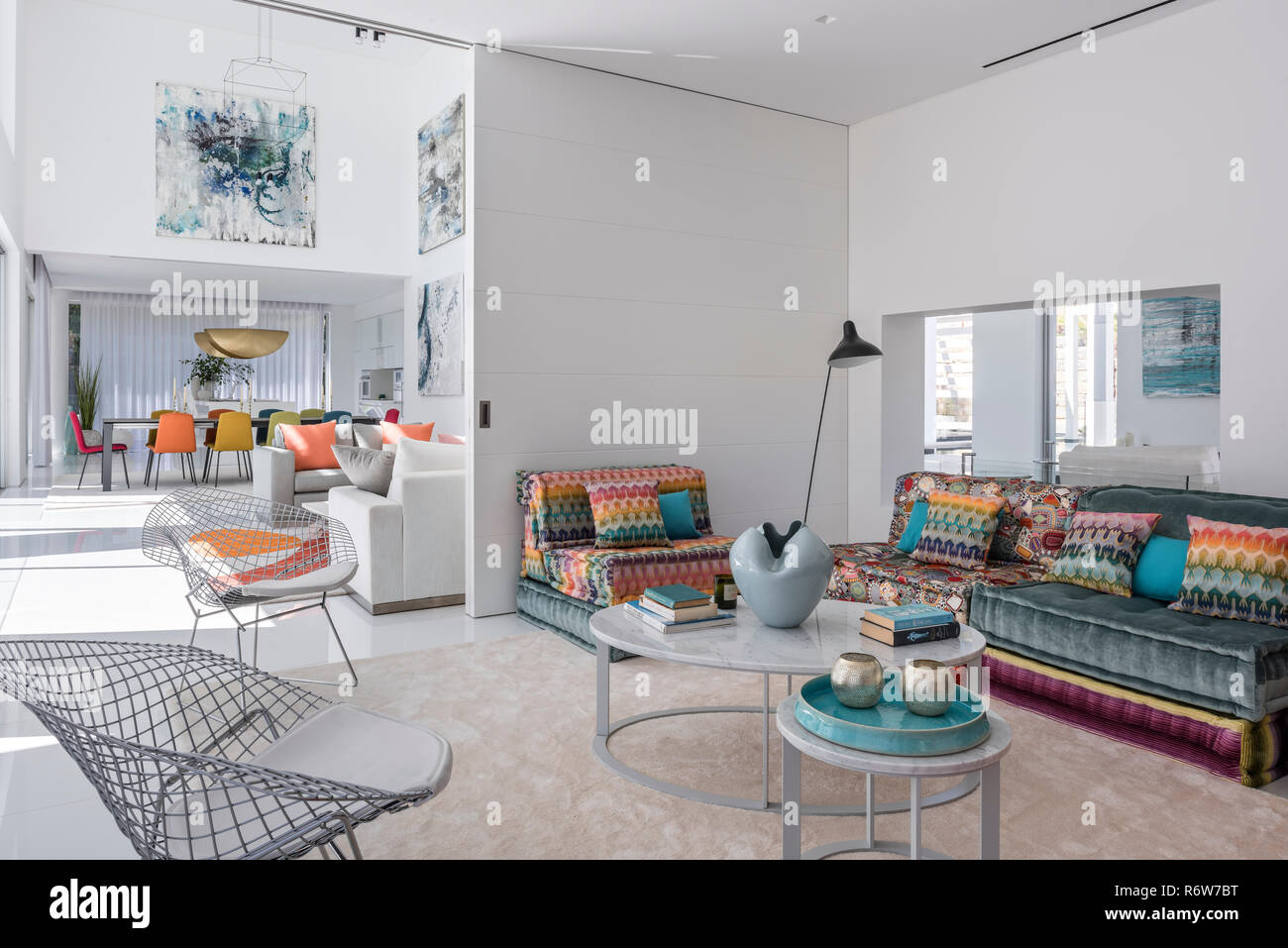 Patterned fabrics and wire mesh chairs in open plan living room of  new build villa, Quinta do Lago - Stock Image