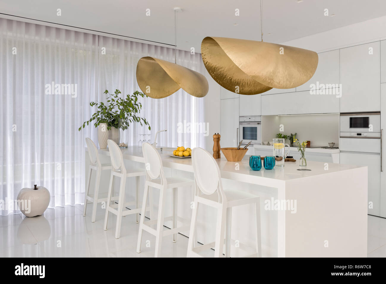Hammered gold shades above kitchen island in new build villa, Quinta do Lago - Stock Image
