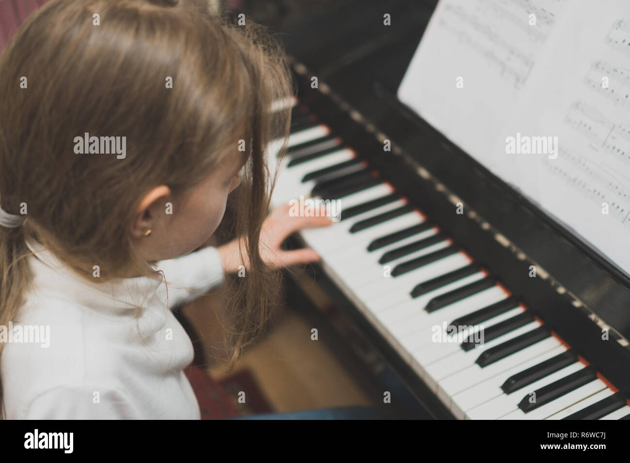 Little girl learning to play the piano. - Stock Image
