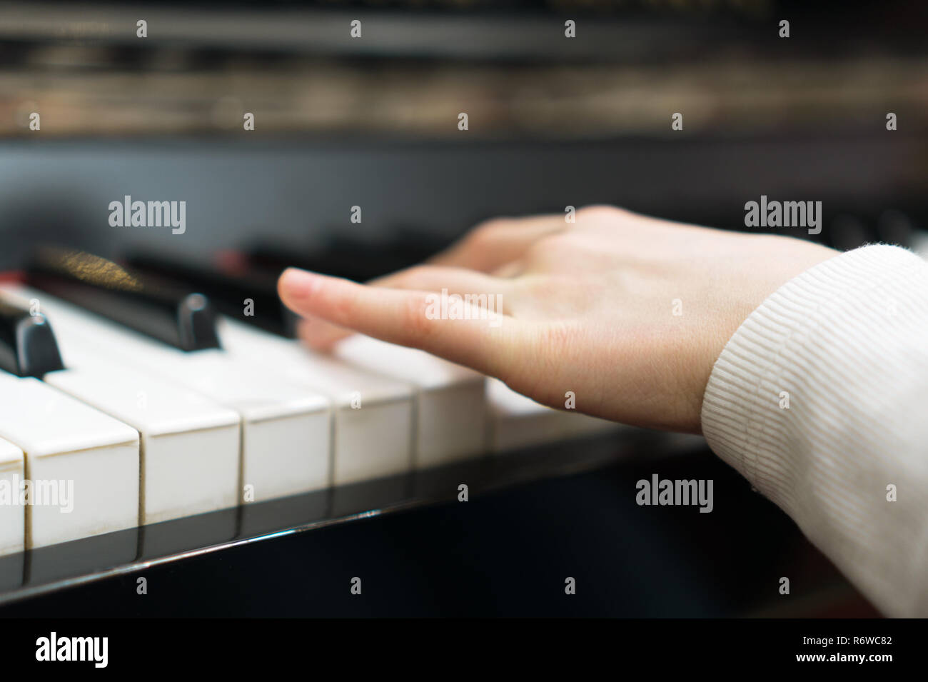Child learning to play the piano. - Stock Image