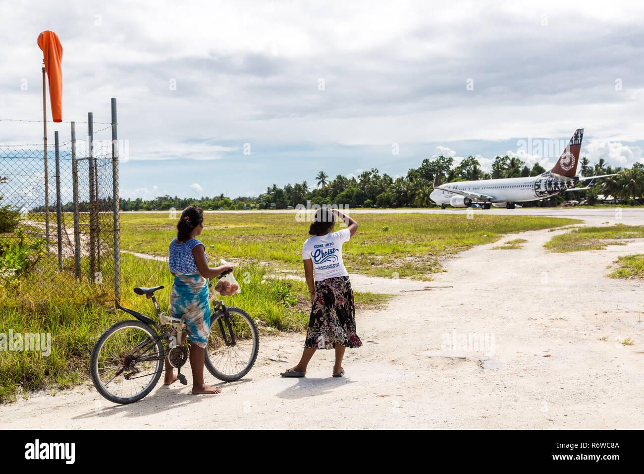 Bonriki airport runway, departing Fiji Airways Boeing 737. Local teenage girls with a bicycle looking at a departing airplane, Tarawa atoll, Kiribati. - Stock Image