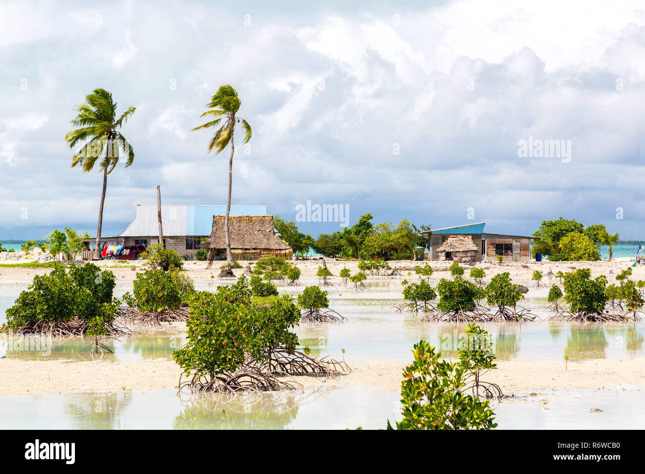 Village on South Tarawa atoll, Kiribati, Micronesia, Oceania. Thatched roof houses. Rural life on a sandy beach of remote paradise island under palms. - Stock Image