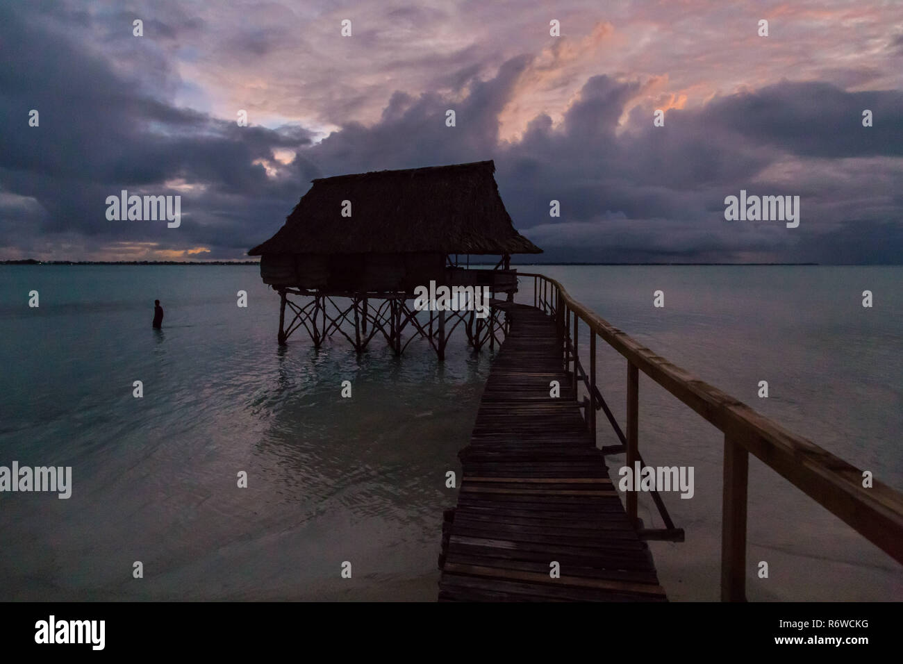 Traditional overwater thatched roof bungalow hut in lagoon of South Tarawa atoll, night, evening, twilight, sunset, Kiribati, Micronesia, Oceania. - Stock Image