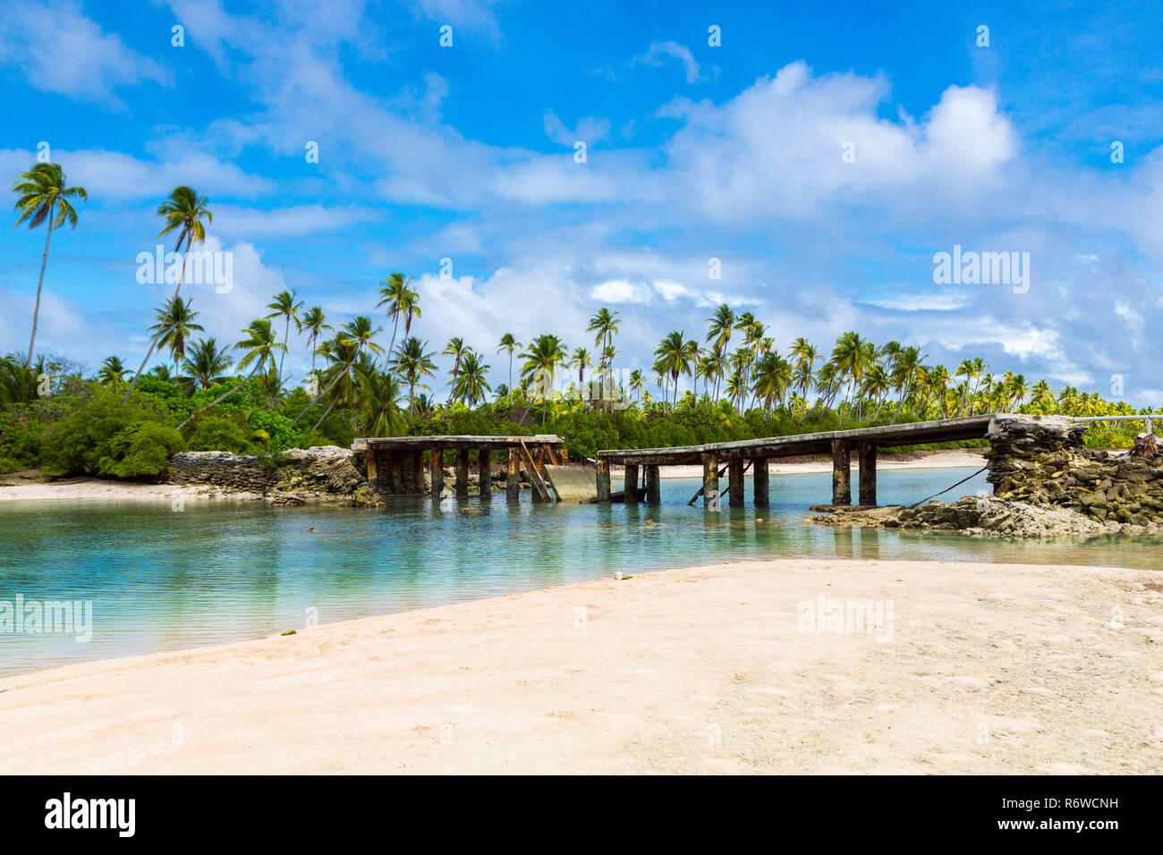 Broken bridge under palm trees between islets over lagoon, North Tarawa atoll, Kiribati, Micronesia, Gilbert islands, Oceania, South Pacific Ocean. - Stock Image