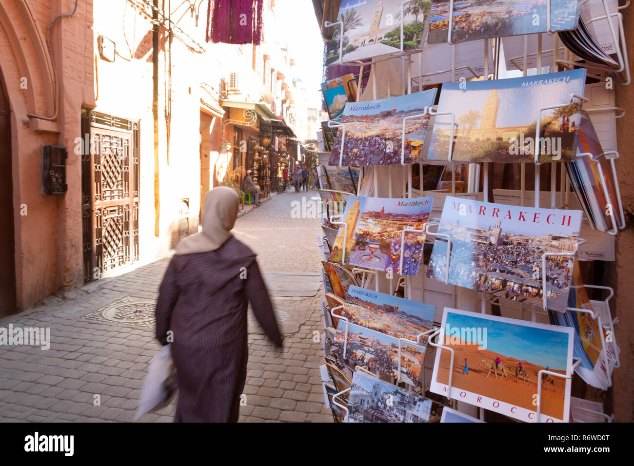 Marrakech tourism - a local woman walks past a shop selling postcards in the souk, Marrakesh Medina, Morocco North Africa Stock Photo