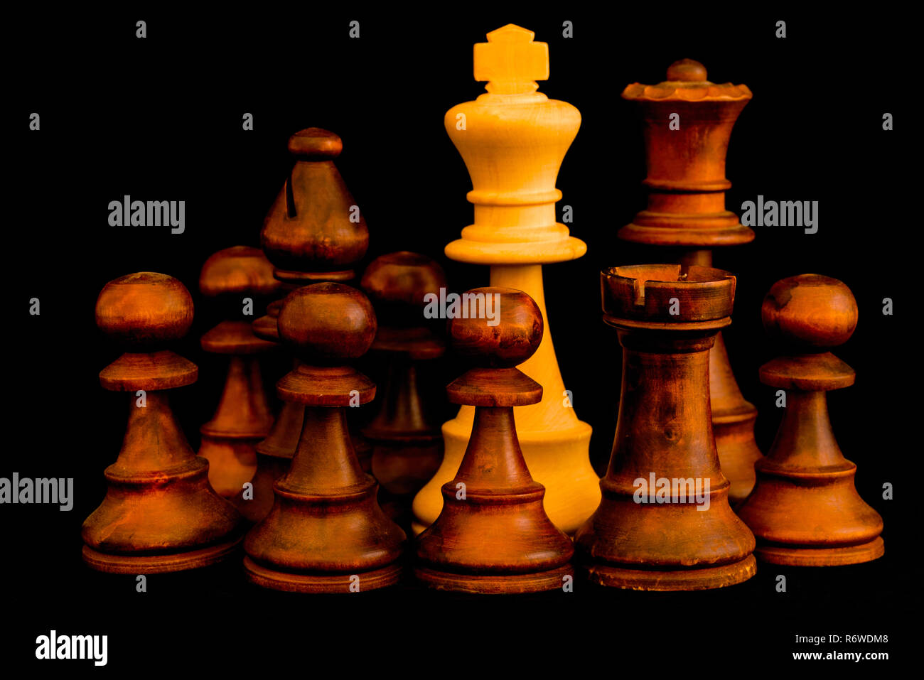Under siege. White King beset by black enemies with sense of no escape, standard chess wooden piece on black background - Stock Image