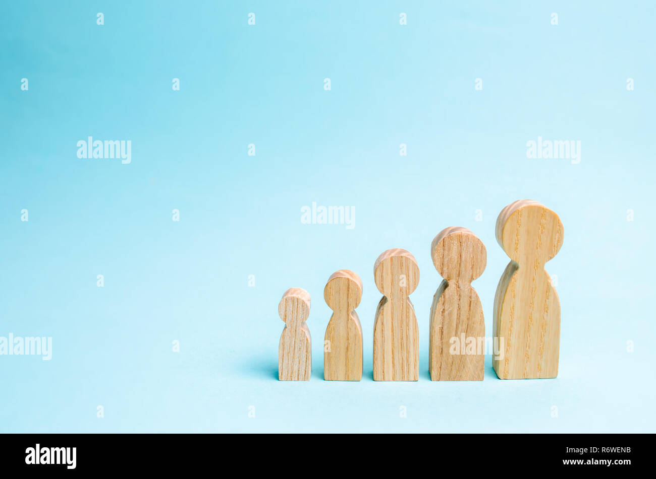 Wooden figures of people from small to large stand in a semicircle. The concept of self-development, growth of personality and professionalism. Childr - Stock Image